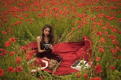 Poppy, Remembrance or Anzac Day. Opium poppy, agile business, ecology. Drug, narcotics, opium, woman with typewriter, camera, book. Woman writer in poppy stock image