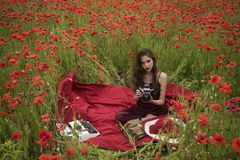 Poppy, Remembrance or Anzac Day. Opium poppy, agile business, ecology. Drug, narcotics, opium, woman with typewriter, camera, book. Woman writer in poppy stock photo