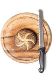 Poppy seed bread roll (Mohnbroetchen) on cutting board with knif Royalty Free Stock Photos