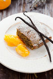 Poppy seed cake with a slice of orange on a white dish Stock Images
