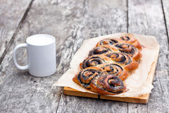 Poppy seed roll freshly baked on the table with white mug of the milk Stock Image