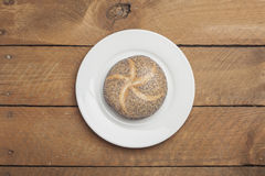 Poppy seed roll on plate and wood Stock Images