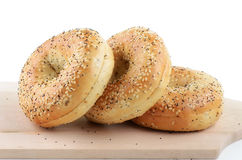 Poppy seed and sesame seed bagels. On wooden cutting board Royalty Free Stock Photo