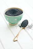 Poppy seed in silver spoon Stock Image