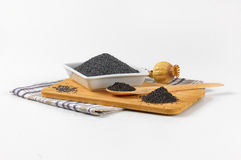 Poppy seeds and poppy head. Bowl of poppy seeds na poppy head on wooden cutting board Stock Photography