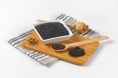 Poppy seeds and poppy head. Bowl of poppy seeds na poppy head on wooden cutting board Stock Photo