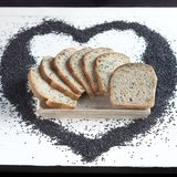 Poppy seeds sourdough bread. On a white table board royalty free stock image