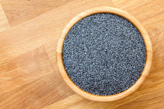 Poppy seeds in wood bowl on wood surface, from above, space for Royalty Free Stock Photo
