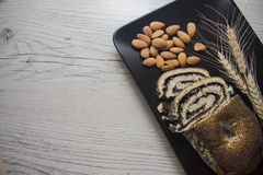 Poppy strudel and almonds on black plate stock photos