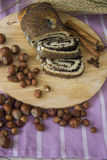 Poppy strudel on wooden plate with hazelnuts royalty free stock images