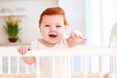 Poprtait της χαριτωμένης ευτυχούς στάσης μωρών νηπίων σε μια κούνια στο σπίτι Στοκ Εικόνες