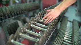 Pops a dumbbell in the gym of the stack. No face. Do not recognizable stock video footage