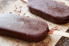 Popsicle with grated chocolate on wooden Royalty Free Stock Photography