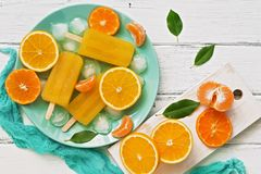 Popsicle orange with slices of fresh orange, mandarin and green leaves on a white rustic plank table. Top view, flat lay stock photos