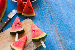Popsicles куска арбуза на голубой деревенской деревянной предпосылке Стоковые Фотографии RF