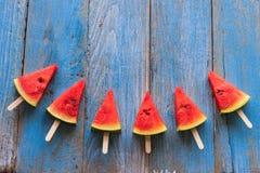 Popsicles куска арбуза на голубой деревенской деревянной предпосылке Стоковые Изображения