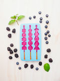 Popsicles Ice in ice form with  blueberries and blackberries  on white wooden background, top view Royalty Free Stock Images