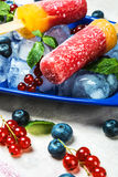 Popsicles with red currants and blueberries on a wooden table. Popsicles with red currants and blueberries Stock Photo