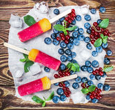 Popsicles with red currants and blueberries on a wooden. Table Stock Image