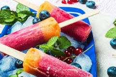 Popsicles with red currants and blueberries on a wooden table. Sorbet Royalty Free Stock Image