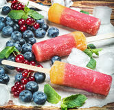Popsicles with red currants and blueberries. On a wooden table. vignetting applied as an artistic effect Stock Photo