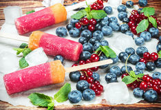 Popsicles with red currants and blueberries. On a wooden table. vignetting applied as an artistic effect Royalty Free Stock Photography