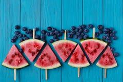 Popslices et myrtilles de tranche de pastèque sur un dos en bois bleu Images libres de droits