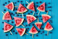 Popslices et myrtilles de tranche de pastèque sur un dos en bois bleu Photographie stock
