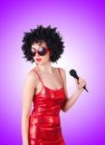 Popstjärna med mic i röd klänning mot Arkivbilder