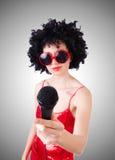 Popstjärna med mic i röd klänning mot lutning Royaltyfri Fotografi