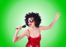 Popstjärna med mic i röd klänning mot lutning Royaltyfria Bilder
