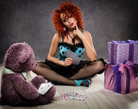 Popsy play cards with a teddy bear. Curly redhead sexy girl looks like a doll for adult men. Stock Photo