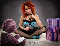 Popsy play cards with a teddy bear. Curly redhead sexy girl looks like a doll for adult men. Royalty Free Stock Photo