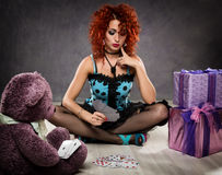 Popsy play cards with a teddy bear. Curly redhead sexy girl looks like a doll for adult men. Royalty Free Stock Image