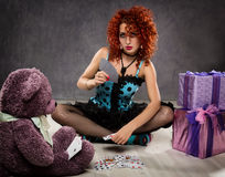 Popsy play cards with a teddy bear. Curly redhead sexy girl looks like a doll for adult men. Stock Image