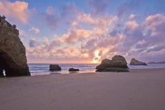 Populär touristic härlig för praiada för sandig strand rocha i solnedgång Arkivbild