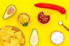 Populära mexikanska mellanmålnachos Den Tiangle nachotortillan nära salsa- och guacamolesause, chilipeppar, saltar på guling arkivbilder