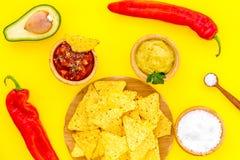 Populära mexikanska mellanmålnachos Den Tiangle nachotortillan nära salsa- och guacamolesause, chilipeppar, saltar på guling royaltyfria bilder