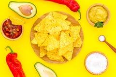 Populära mexikanska mellanmålnachos Den Tiangle nachotortillan nära salsa- och guacamolesause, chilipeppar, saltar på guling arkivfoton