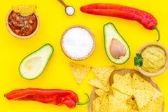 Populära mexikanska mellanmålnachos Den Tiangle nachotortillan nära salsa- och guacamolesause, chilipeppar, saltar på guling arkivbild