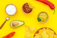 Populära mexikanska mellanmålnachos Den Tiangle nachotortillan nära salsa- och guacamolesause, chilipeppar, saltar på guling fotografering för bildbyråer