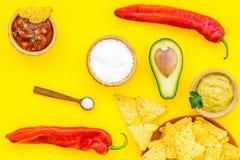 Populära mexikanska mellanmålnachos Den Tiangle nachotortillan nära salsa- och guacamolesause, chilipeppar, saltar på guling royaltyfri fotografi