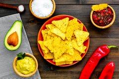 Populära mexikanska mellanmålnachos Den Tiangle nachotortillan nära salsa- och guacamolesause, chilipeppar, saltar på mörkt trä fotografering för bildbyråer