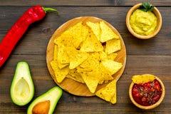 Populära mexikanska mellanmålnachos Den Tiangle nachotortillan nära salsa- och guacamolesause, chilipeppar, saltar på mörkt trä royaltyfri bild