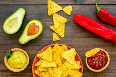 Populära mexikanska mellanmålnachos Den Tiangle nachotortillan nära salsa- och guacamolesause, chilipeppar, saltar på mörkt trä arkivfoto