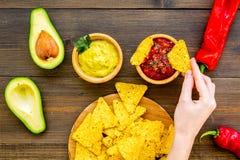 Populära mexikanska mellanmålnachos Den Tiangle nachotortillan nära salsa- och guacamolesause, chilipeppar, saltar på mörkt trä royaltyfri fotografi