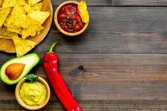 Populära mexikanska mellanmålnachos Den Tiangle nachotortillan nära salsa- och guacamolesause, chilipeppar, saltar på mörkt trä royaltyfria bilder