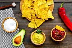 Populära mexikanska mellanmålnachos Den Tiangle nachotortillan nära salsa- och guacamolesause, chilipeppar, saltar på mörkt trä arkivbild