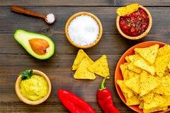Populära mexikanska mellanmålnachos Den Tiangle nachotortillan nära salsa- och guacamolesause, chilipeppar, saltar på mörkt trä royaltyfria foton