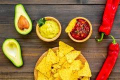 Populära mexikanska mellanmålnachos Den Tiangle nachotortillan nära salsa- och guacamolesause, chilipeppar, saltar på mörkt trä arkivbilder